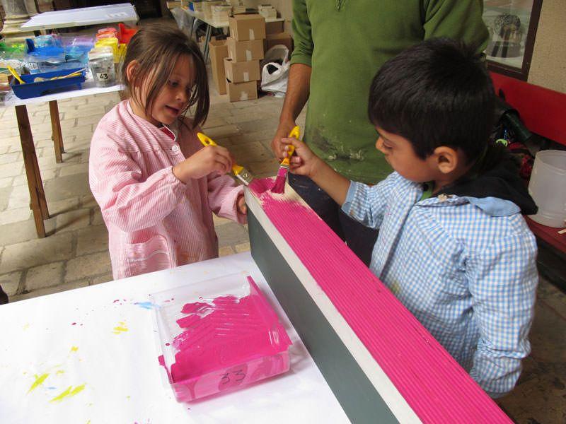 Els nens pinten les peces de fusta del gran joc ELS CONSTRUCTORS_ . El color correspon al color del detall del barri que han triat